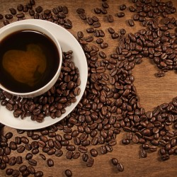 a-cup-of-coffee-coffee-beans-placed-heart-shaped-pattern_1680x1050